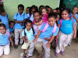 Hector surrounded by many of his preschool students